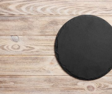 Black slate round stone on wooden background, top view, copy space.